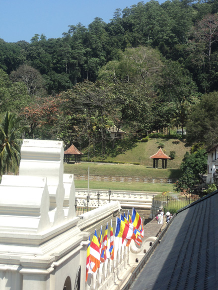 The lush green hills on the lft of the temple entrance. The main entrance is pristine white with Buddhist flags highlighting the passage.