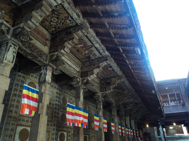The side exterior of the temple has beautiful architecture with wooden pillars and carved angles.