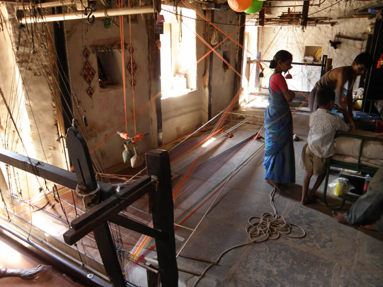Read about Aihole sarees and was keen to how they were made. While driving down from Aihole to Hampi the driver stopped at a village, asked a old man sitting under a tree if sarees were available there. He said yes and directed us to his house which is what u see. U see 2 powerlooms, one right in front of pic and other at end. Mother and son work independently.