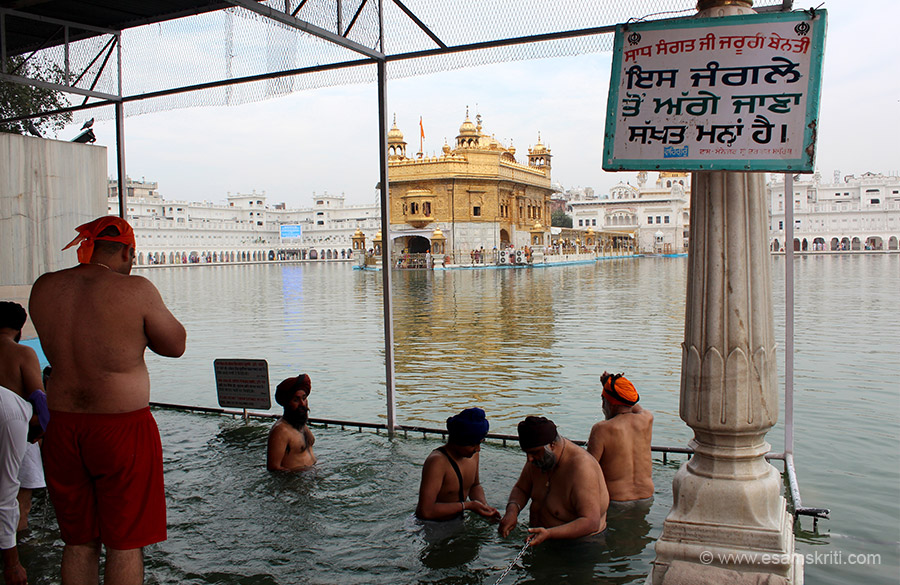 Devotees taking the holy dip, some praying. There are steps that lead to the waters of the holy tank. The Steps are called Har-ki-Pauri. Excavation of Sarovar was started by Guru Ram Das in 1574, stopped