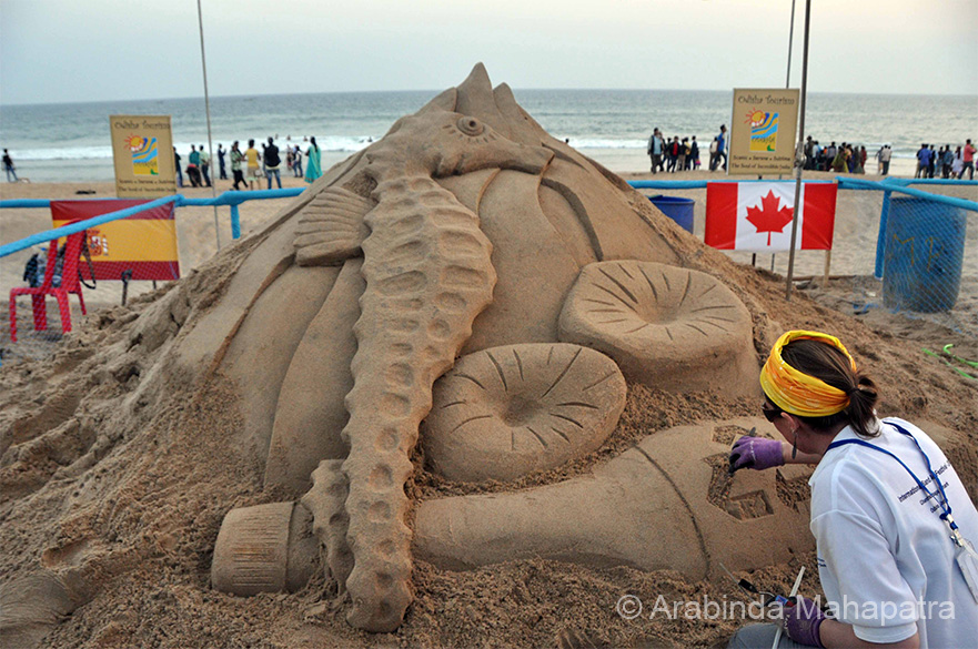 "Artist Asheley Elizabeth from Canada at work. """"Golden Sand Art Institute"" which is an open air institute in Puri Beach behind Mayfair Hotel was started in the year 1999."""