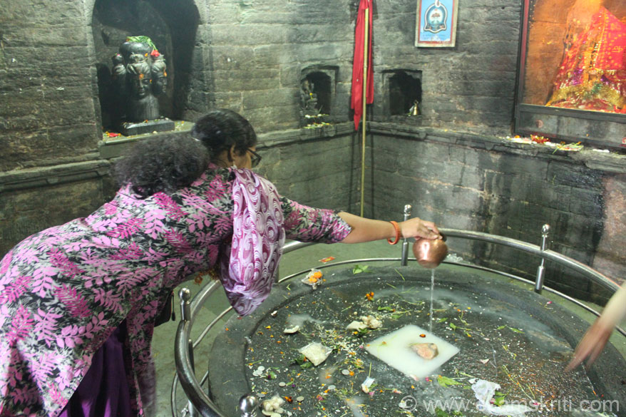The big black stone in the centre is Shiv Shakti. Devotee makes offering. Note the stone image of Lord Shiva``s face in rear part of pic.