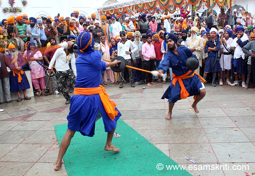 No sharp edged weapons are used in the transformed Gatka game. The martial art, in which Gatka (wooden stick) is used as a weapon, is called Gatkabaazi. U see two Nihangs fighting with wooden sticks. Traditionally Gatka was played by Nihangs but today even other jatis of Sikhs like khatris learn and play Gatka.
