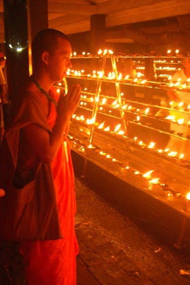 A monk offering prayers to the butter lamps which have been lit at twilight.