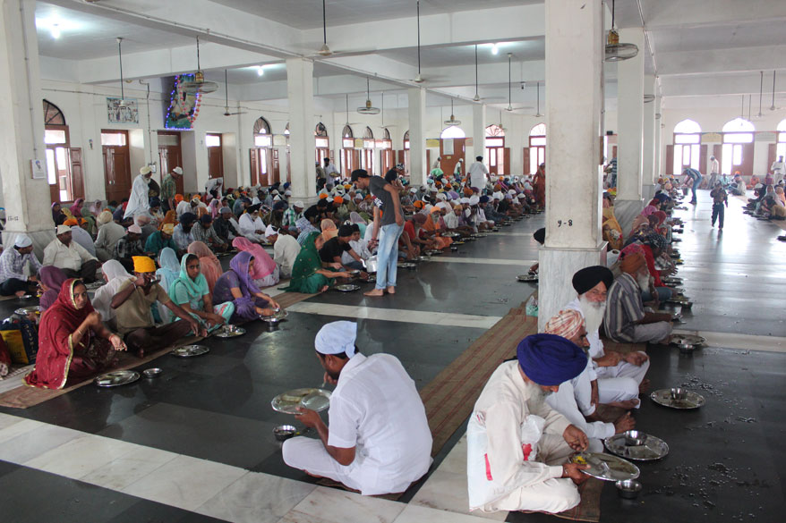 There are two halls in the langar where devotees are served, on ground and first floor. They are well lit. There is a cloth matt on which devotees sit. Next pic has Sringeri Mutt hall.