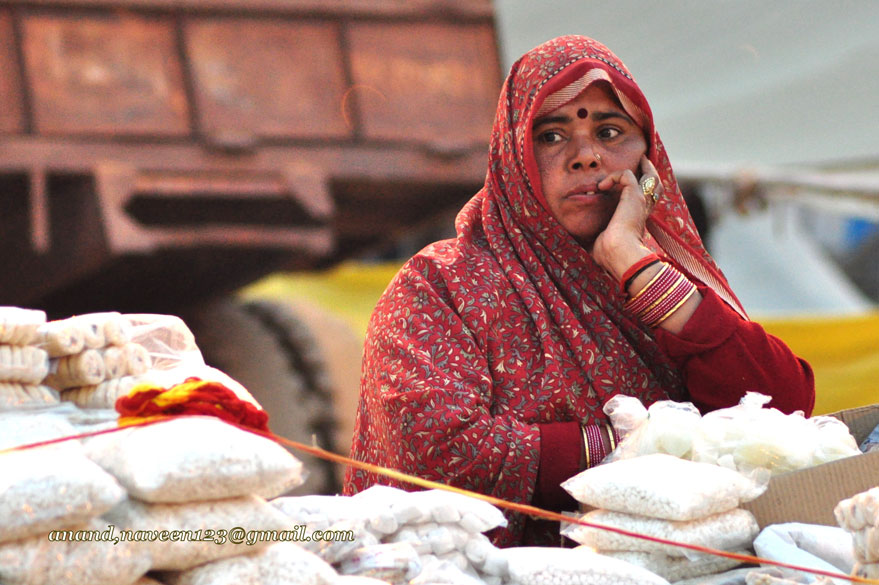 Lady selling kurmura, prasad items. Waiting in Hope for buyers!