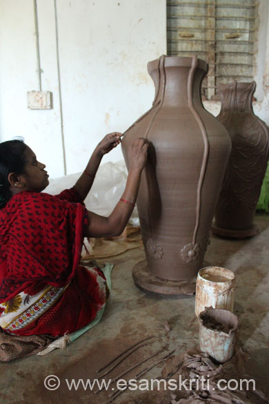 U see a lady making a design on the jar now. After that the jar is dried and then put in a bhatti (oven). Part of captions borrowed from <a target=_blank href=http://www.cghandicraft.com>Click here</a>