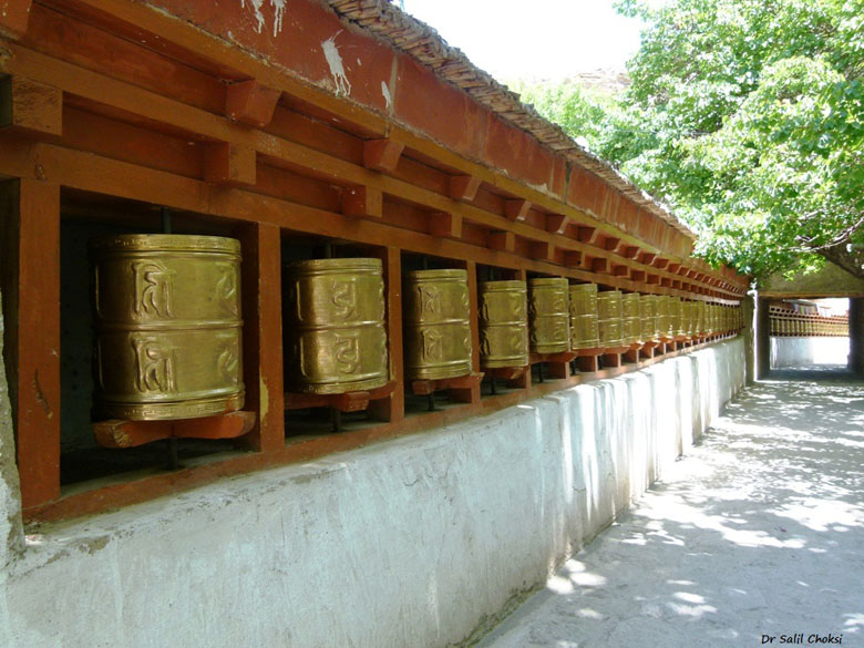 Prayer Wheels at Alchi Monastery. A prayer wheel is a cylindrical wheel on a spindle made from metal, wood, stone, leather or coarse cotton. Traditionally, the mantra Om Mani Padme Hum is written in Sanskrit on the outside of the wheel. Also sometimes depicted are Dakinis, Protectors and very often the 8 auspicious symbols Ashtamangala. According to the Tibetan Buddhist tradition based on the lineage texts regarding prayer wheels, spinning such a wheel will have much the same meritorious effect as orally reciting the prayers.