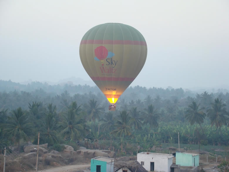 Where the balloon goes is a function of wind direction. We are moving westwards over banana fields. Hot air being released into the balloon.