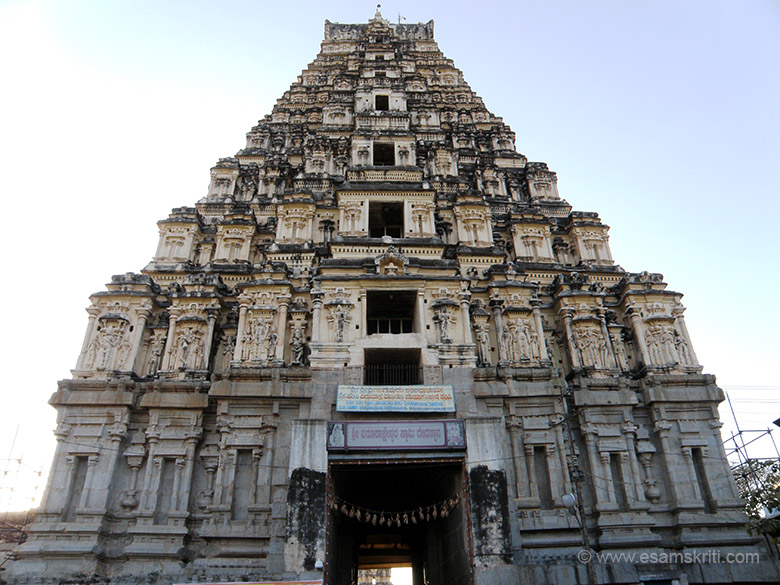 A close up view of the main gopuram. This pastel painted 9 storied tower has a pair of cow horn like projections on the top. The lower two tiers of tower is made of decorated stone work that u see. The rest is