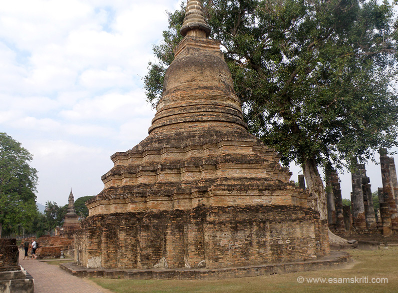 To the left of the main chedi (stupa) and behind the two standing Buddha images are number of stupas, you see one of them.