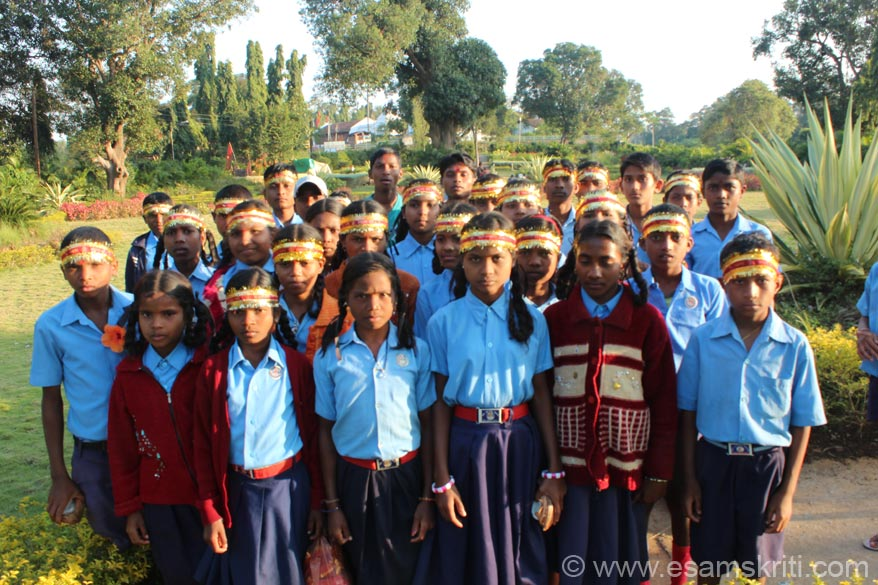 Pic of Adivasi school children who were visiting temple. Standing in the beautiful garden i.e. just behind the temple. Garden has a fountain, lots of trees and well landscaped. In centre of pic white 