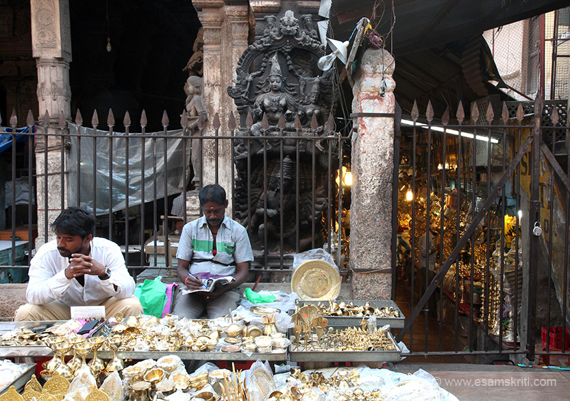 At gopuram entrance on pavement shop. Behind where men sitting is stone images which represents Ravana attempting to lift Mount Kailash, the abode of Bhagwan Shiva and his Consort