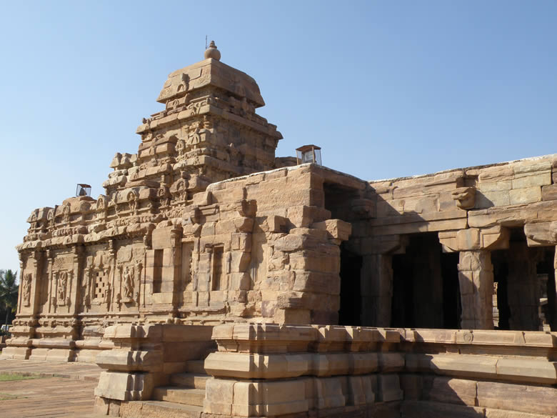 A close up of the temple. As you can see it is made on a plinth having a moulded base divided by Deva Koshtas. Pillars are characteristically plain and heavy. To right of picture you see pillars in the sabha-mandapa. There are four rows of four heavy pillars each. You can see beautiful sculptures of Vishnu, Varaha, Shiva in the niches of the outer walls. Something special about temple design and make.