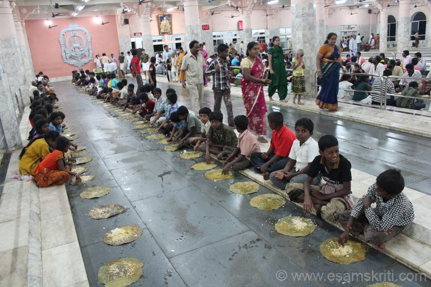 A group of children enjoying their meals. After meals are over a group of ladies clean the area with soap, dry it before the next group of devotees arrive.