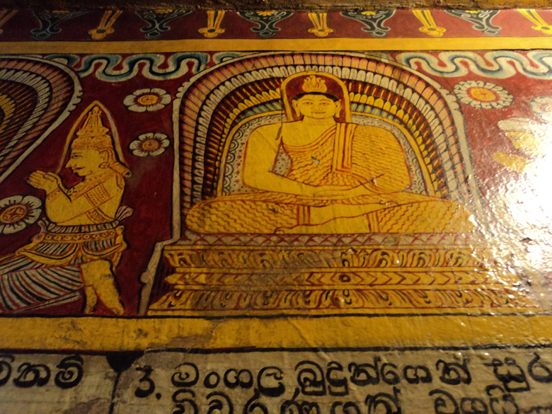 One of the Budha murals on the wall, depicting Theravada yellow robes and Sinhalese inscriptions.