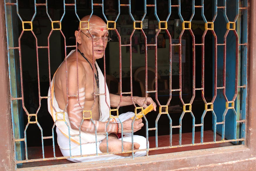 An elderly man chanting his prayers in the morning. He was reading from the book in hand, happily allowed me to click him.