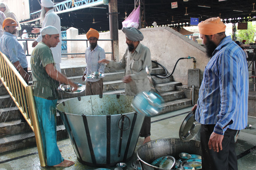 After every devotee completes his food in the temple, he has to give the utensil to this group of devotees. Food leftovers are removed into a large container that you see after which the utensil is thrown into another 