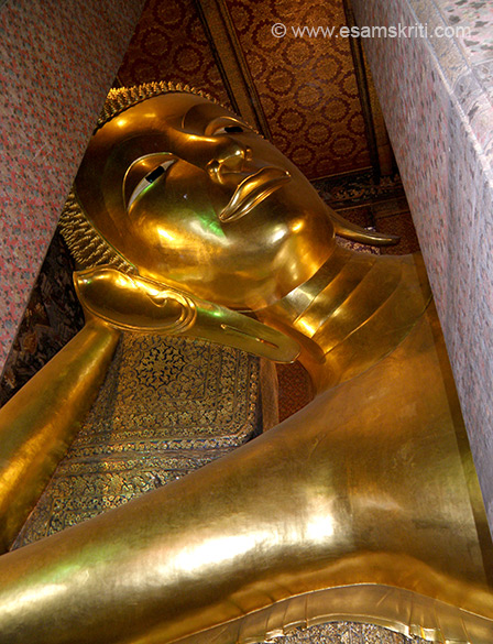 Close up of the face and hand of reclining Buddha.