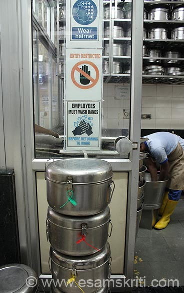 Seals are of 3 colors ie yellow, red and green. These are color codes depending on quantity. This is entrance to kitchen area. Instructions that you see above containers are head gear, devotees to wash their hands before they return to work. Kitchen has a very professional and hi-tech set up. What distinguishes it from a similar kitchen is the love and bhavna (feeling) with which devotees cook and pack the food for India``s children.