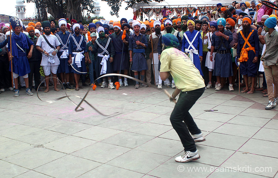 A devotee showing Aara skills during Gatka. It is basically a strip of steel - warriors swing it in the air, up and down. Must be heavy. Onlookers have to be careful.