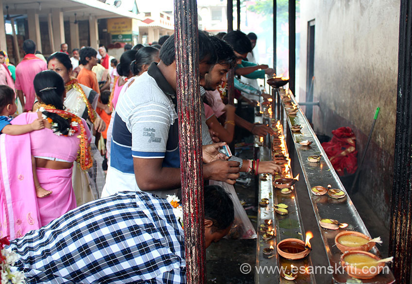 Devotees lighting diyas or lamps that are placed on one side of temple wall.