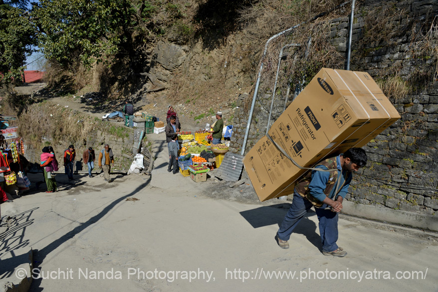 People of the hills carry lots of weight. This man is carrying a Samsung refrigerator on his back. To see pics of Children of Arunachal Pradesh 