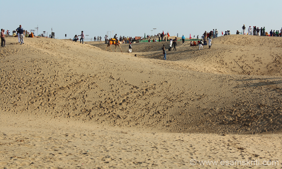 Pic of sand dunes. People walk up and down the dunes or go on camel back.
