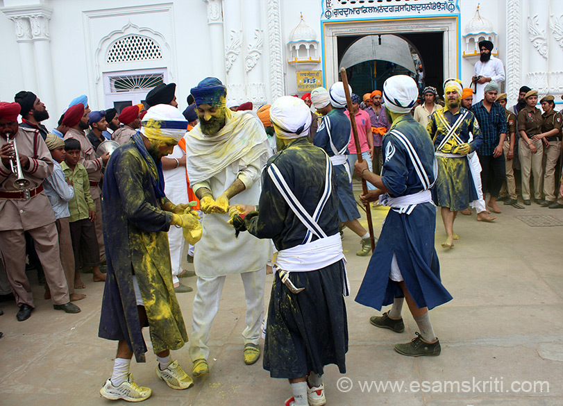 We walked down the steps of Anandgarh Sahib towards road, you see devotees playing with Holi colors.