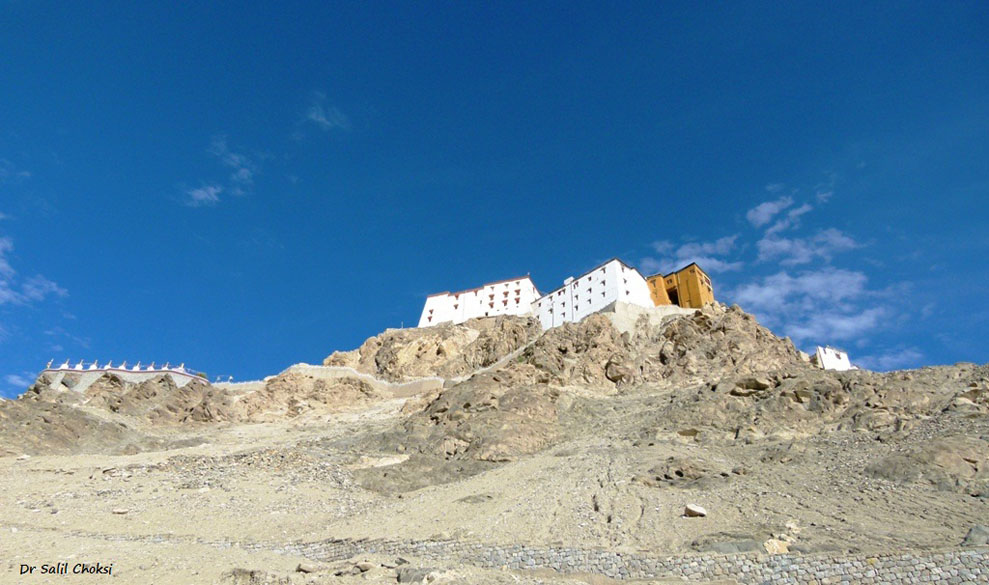"The imposing Thiksey monastery, with a ``mani wall`` in the foreground. Mani walls are stone structures made of a compilation of intricately carved stone tablets, most with the inscription ""Om Mani Padme Hum"" which loosely translates to ""Hail to the jewel in the lotus"". These walls should be passed or circumvented from the left side, the clockwise direction in which the earth and the universe revolve, according to Buddhist doctrine."
