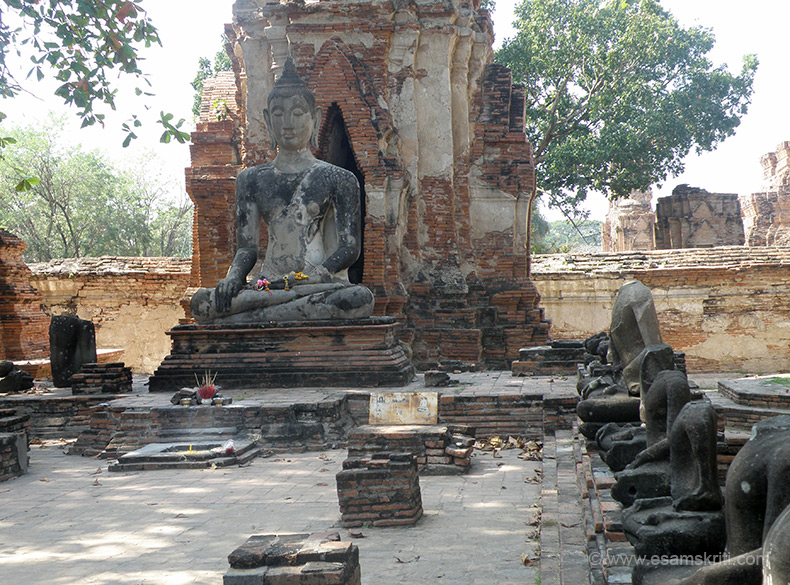 You see a number of headless images of Buddha with a larger one in the centre. The structure behind is in ruins.