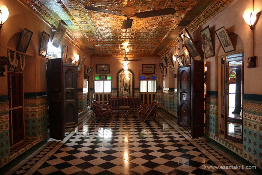 "Room two, ceiling has tiles as do walls. Lots of pictures of gods and goddesses and family on walls. ""The Nattukottai Chettiar traders followed the expansion of the British Empire into S.E.Asia for their business. They brought back Burmese teak and European tiles for their mansions, as well as the inspiration from colonial and palace architecture. They also incorporated the wealth of wood sculpting and craftsmanship from local craftsmen in their homes."""