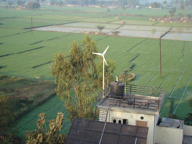 Small windmill on top of the same house.