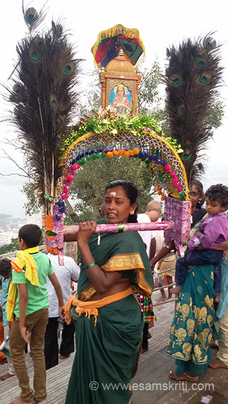 Lady carrying Kavadi on her shoulders, top is an image of Muruga - it is covered by an umbrella. When Muruga settled on the hill, Idumban found he could not lift the hill as Murugan made it impossible for him. The two fought. Idumban was killed and brought to life thereafter.