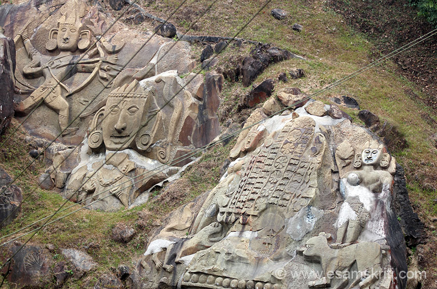 Close up of carvings on vertical rock cliff. There is head-dress of Shivji, two females on either side and Shri Ram/Lakshman on the left of pic.