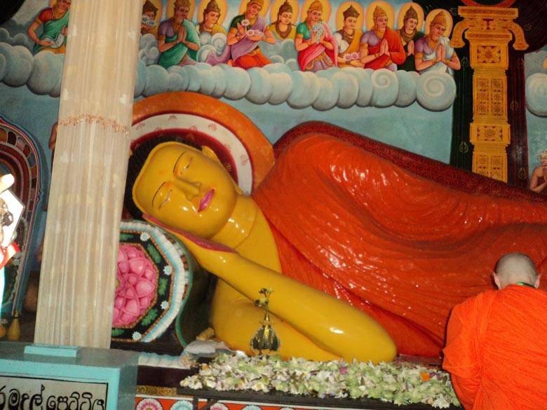 A close up of the serene expression as Buddha gave up his body. Devotees offer flowers to the image, sometimes the flowers are made of colorful cloth appliqued together. This is 