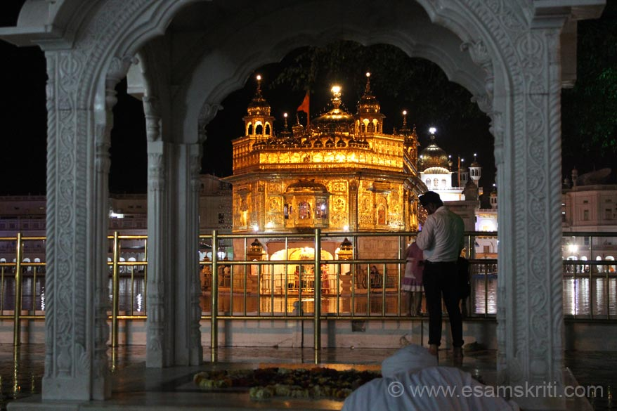 An evening view of the Hari Mandir thru the arch. Right of pic is Akal Takht identified by light on top of the dome.