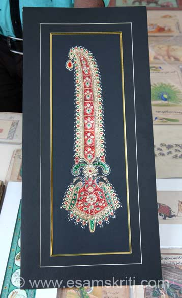 This is a Tanjore Miniature. Gold foil is pasted n paper, meena color red and green, gems artificial and brush design. Contacts of Mohan K Prajapati are 91 99289 35136, 0141 2420504, 