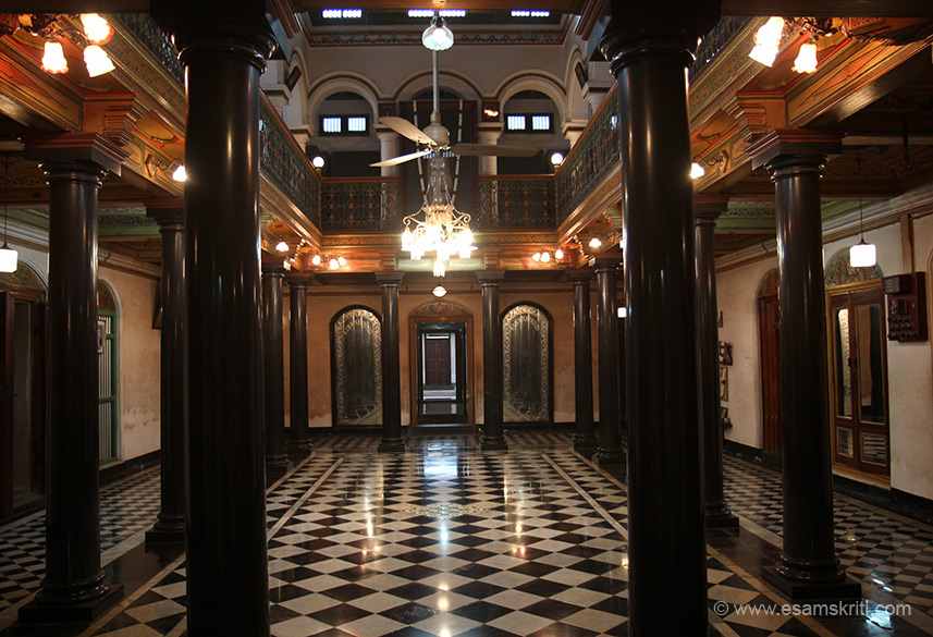"This is a big hall with rooms all around, covered in some detail. ""Chettinad architecture stands out for its use of large spaces in halls and courtyards, ornate embellishments like Belgian glasswork, intricate woodwork, spectacular ceramic tiles, stone, iron and wooden pillars like nothing else that can be seen in this part of the world. """