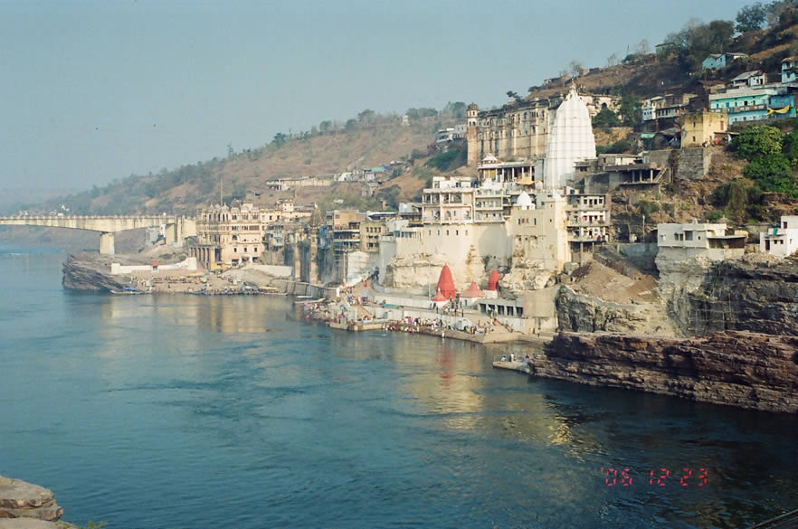 Omkareshwar, the sacred island, shaped like the holiest of all Hindu symbols, `Om`, has drawn to it hundreds of generations of pilgrims. Here, at the confluence of the rivers Narmada and Kaveri, the devout gather to kneel before the Jyotirlinga (one of the twelve throughout India) at the temple of Shri Omkar Mandhata. An overview of Omkareshwar Jyotirling ie on the banks of the river Narmadaji. What you see in front is the Narmada river, at the base of the red temple is a ghat where devotees bath in the Narmada, the white structure is the temple that houses the Jyotirling, behind that is king Mandhata's palace. On the left is a bridge that takes devotees on to the island. Clicked from new bridge.