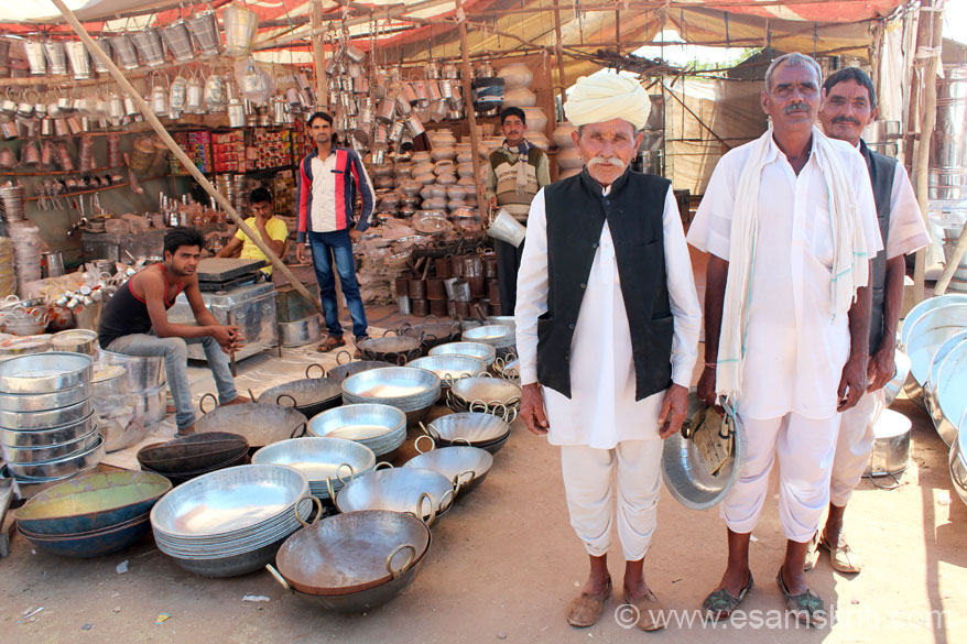 In the same fair number of shops sell utensils and other items of home use. Right of picture u see a senior citizen in traditional dress. Different communities wear the pagdi in different ways. More about pagdis in the Havelis of Jaisalmer section.