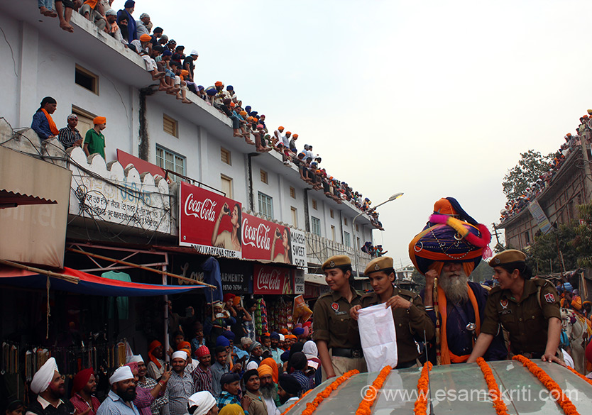 Procession has devotees on roads, homes and building tops as you can see on both sides of the pic. Man on right of pic with lady cops is an aging warrior with perhaps the second biggest turban that I saw during 2014 Hola Mohalla festival.