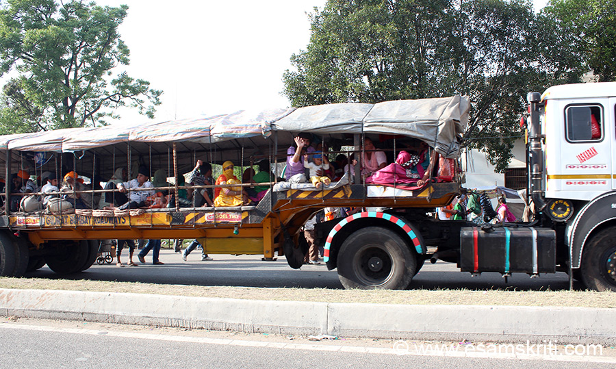 "Devotees come in truck trolleys (like what u see), tractors, trucks and motor cycle. Note how long this trolley is. Devotees leave their luggage in one of the many restrooms, have food at the langar and either sleep in the trolley or restrooms. ""Hola is derived from the word halla (a military charge) and the term mohalla stands for an organized procession or an army column. The words ``Hola Mohalla`` would thus stand for ``the charge of an army.``"""