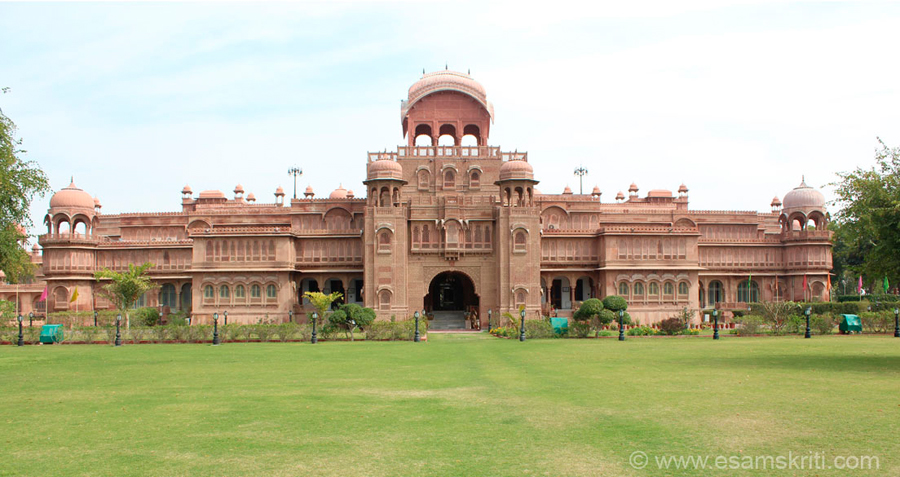 Front view of Lakshmi Vilas Hotel. Looks magnificent. Has a huge lawn in front. This collection focuses on Lallgarh Palace. The palace is made in red-sandstone. It was built by 