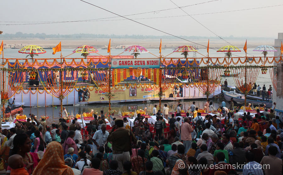 A stage was made in the water. People sitting on Dasashvamedha Ghat. Two functions are organised one by the Ganga Seva Nidhi and another by Ganga Seva Samiti both adjacent
