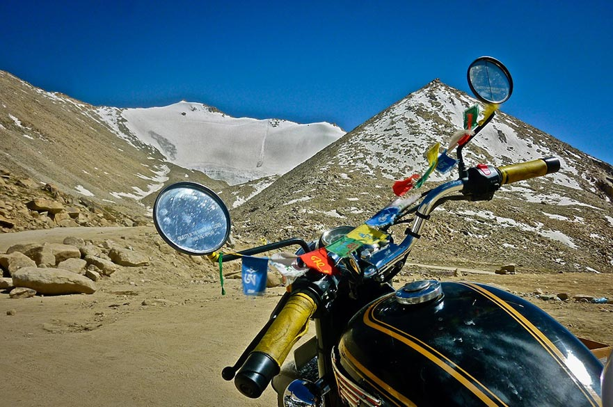 Contrary Reflections: This motorcycle parked on the Chang La pass in Ladakh (3rd highest motorable road in the world at 17,590 ft!) was perfectly angled to show the two facets of the Karakoram mountain ranges in Ladakh. Ahead, one can see the barren rocky ranges, while in the bike``s rear view mirror the snow capped mountains are visible. Fluttering between its handles are Tibetan Buddhist flags with the words ``Om Maani Padmayum`` which are commonly found all over Ladakh and are also installed as good luck and safety charms by the daring riders who ride all across these mountains.