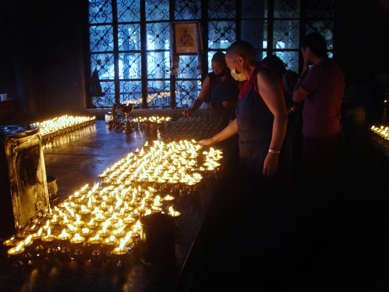 Monks light a hundred thousand butter lamps as an offering to the Buddha at the Dalai Lama temple.