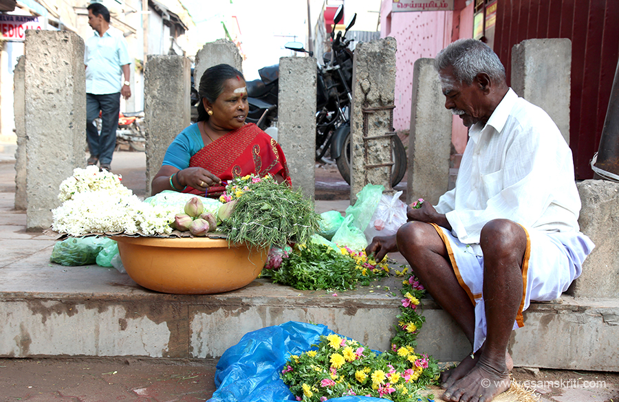During January 2016 Tamil Nadu Yatra visited over 60 temples. This album has pictures of ladies who sell flowers outside temples. Man helping his wife outside Meenakshi Mandir Madurai.