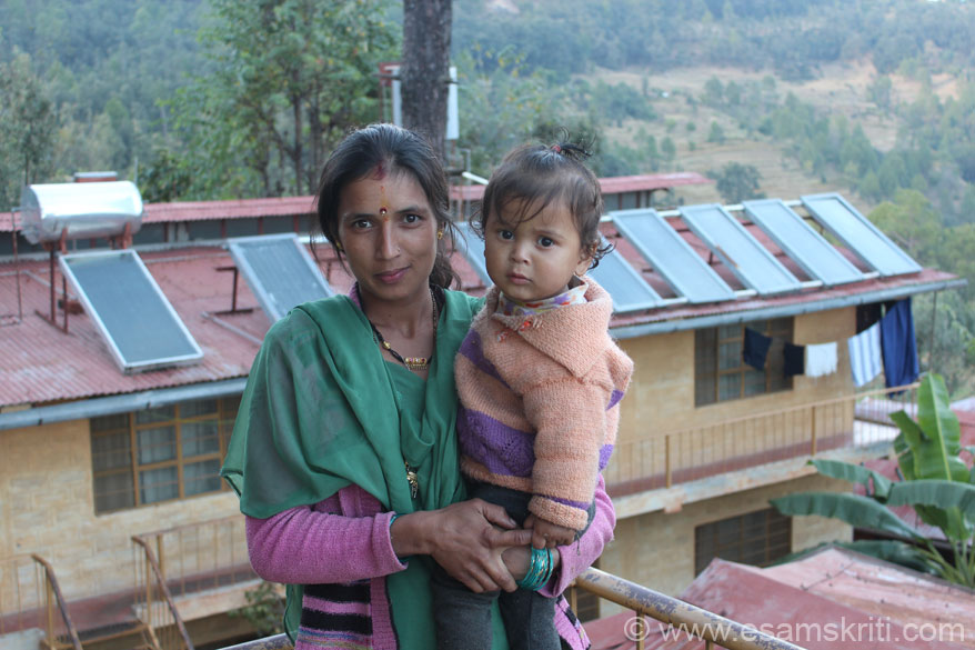 Lady who works in the power looms to make shawls with her child. In background are living rooms that are powered by solar panels. Solar Water heaters fabrication and installation is 