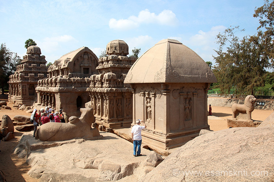 Right to left first is Draupadi ratha, Arjuna-ratha, Bhima-ratha, Dharmaraja-ratha. Draupadi ratha is supported by 4 corner-pilasters and has a niche crowned by makara-toranas on 3 sides. Niches contain standing figures of Durga. Right of pic and in front of ratha is a standing lion, representing the vehicle of Durga. Left centre is half finished Nandi.